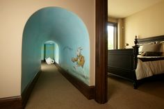 This tunnel shrinks as it goes in, all the way down to 4 feet at the end, leading to an Alice in Wonderland playroom. This space is under the stairs, so the shrinking fits right it. Most genius idea ever.