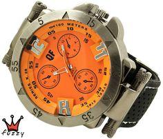 Ανδρικό ρολόι  σε ασημί και πορτοκαλί χρώμα με ανάγλυφα σχέδια στο εσωτερικό του. Λουράκι σε μαύρο χρώμα από σιλικόνη με λευκές ραφές . Καντράν  48 mm.