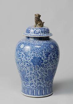 Anonymous | Pair of lidded vases, Anonymous, c. 1700 | Grote vaas met deksel; breed van boven en naar beneden verjongend; korte ronde hals en een gewelfde deksel met vlak, schuin naar beneden uitstekende rand en vlakke bovenkant, met een verguld leeuwtje met rode tong en zwarte ogen als knop. De vazen zijn zeer dicht versierd met ranken en bloemen in onderglazuur blauw. Boven de witte voetrand een brede strook in ondergalzuur blauw, waarin hangende druiventrossen zijn uitgespaard. Onder de…
