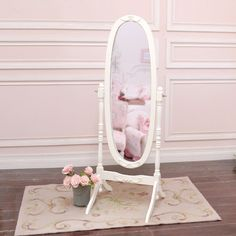 """This gorgeous oval mirror would be perfect as part of your bedroom or home decor! The mirror rotates on its stand making it the perfect dressing mirror. The frame features lovely roses. Great for any cottage style home! Has been painted our popular soft white color! Edges have been distressed to emulate a vintage appearance. Also features our popular rose appliques! • 59""""H x 22""""W x 11""""D • White"""