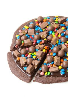 This dessert pizza is AMAZING! A thin and chewy brownie topped with chocolate ganache and lots of candy, including M&M's, Maltesers and chocolate caramel. Recipe from sweetestmenu.com #brownie #pizza #dessert #chocolate #candy