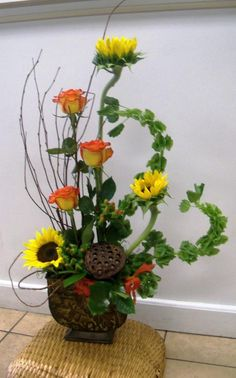 Fall Arrangement. Very clever use of the Bells of Ireland, which curl up this way naturally as they sit in the oasis.