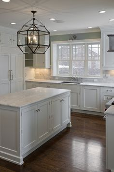 Dark floors,white cabinets, white granite, silver knobs and gray paint wall. Beautiful kitchen window. I don't love the pendant light though #whitekitchen #woodfloors