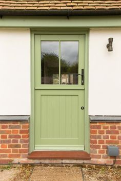 Dual colour (green outside, white inside) half-glazed panelled timber stable door by Wood Window Alliance member, George Barnsdale.