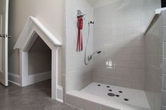 Mud room with built-in dog shower and dog house.