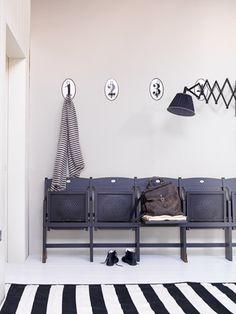 Leuk die oude bioscoopstoeltjes, deze kun je ook gebruiken om spullen op neer te zetten. Door de muur achter de zwarte stoeltjes in een warme grijs te schilderen verzacht je het contrast.