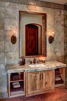 Distressed wood is paired with gray stone for a rustic vanity in this Mediterranean bathroom. A large mirror is flanked by Old World-inspired sconces, which sit on a wall of stunning earth-toned tile. The entire space is grounded by red brick.