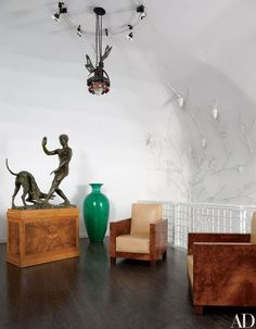 A 1920 Italian wrought-iron ceiling fixture is suspended above a bronze sculpture by Libero Andreotti and a pair of '30s armchairs in the entrance hall | archdigest.com: