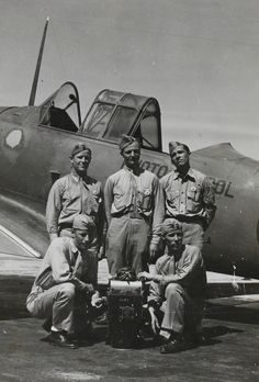 A group of U.S. Marine Corps photographers with their aerial camera next to a trainer aircraft at the Naval Photographic School in Pensacola, Florida.