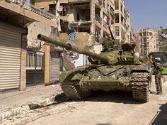 A Syrian army tank is seen next to damaged buildings after clashes between Free Syrian Army fighters and regime forces in the Seif El Dawla neighbourhood of Aleppo city, northwest of Syria September 13, 2012. (Reuters/George Ourfalian)