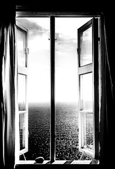 Black and white photograph of an open window, looking out to the ocean. Photographer Annika Öhman. Available as poster at printler.com, the marketplace for photo art.
