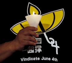 TIANANMEN-ANNIVERSARY/ A representative from the organizer holds a candle on the podium while wearing a T-shirt featuring a yellow umbrella, symbol of the Occupy Central movement, during an annual candlelight vigil at Victoria Park in Hong Kong, China June 4, 2015 to mark Beijing's Tiananmen Square crackdown in 1989, as tension lingers in the financial hub from its pro-democracy protests last year. REUTERS/Bobby Yip