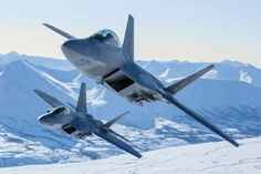 アラスカの雪山を背景に飛ぶ戦闘機F-22が美しい