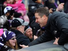 John Harbaugh shakes hands with fans at victory parade.