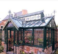 DIY greenhouse project, built from recycled stained glass windows, stairway spindles, salvaged bricks and terracotta plaques to a classic Victorian design