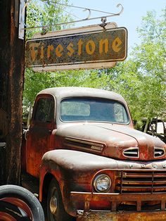 Old Pickup parked under old Firestone sign, Just both rusting away from a different time in place.