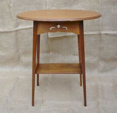 Pretty arts and crafts lamp / side table in golden oak with stylised heart cut out decoration to each under rail .