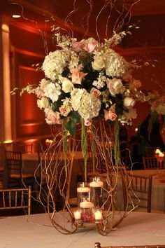 A simple yet elegant high table centerpiece, placed atop a gold stand accented with curly willow and hanging amaranths. #flowers #weddings #centerpieces #backdrops #lighting #yannidesignstudio