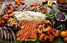 Budol Food Setting, a Filipino food trend where food is laid on a bed of banana leaves. This was taken in England. The food setting included rice, buttered prawns, fried chicken wings, fried fish, beef steak, sauteed shrimp paste dip for boiled eggplants/aubergine and okra/lady's fingers, and squid adobo