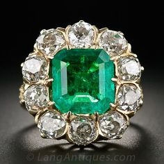 Vintage 3.85 Carat Emerald and Diamond Ring, A bright and lively emerald-cut emerald, weighing nearly 4.0 carats (and presenting larger due to its cut) fills the center of a bold diamond frame sparkling with 4.0 carats of old mine-cut diamonds. The elaborately ornamented 14K yellow gold mounting pays homage to mid-to-late nineteenth century Victorian style with a fully embossed foliate motif ring shank and feathery hand engraving.
