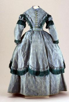 Gown: circa 1867, European or American, ribbed changeable silk, woven with floral sprigs, trimmed with solid silk fringe, lined with cotton, flounced over skirt, and attached belt.