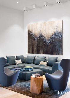 Sculptural B&B Italia chairs and a sectional and ottoman, all from Diva, create a comfortable seating area within the great room. Above hangs Torrent, an acrylic and epoxy artwork by Christopher Aaron. The silk rug is from Minotti.