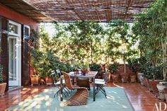 Shaded by a bamboo canopy, the terrace is furnished with Verner Panton rattan chairs and an Allegra Hicks carpet.  Allegra Hicks Creates a Bohemian Chic Home in Naples, Italy Photos | Architectural Digest