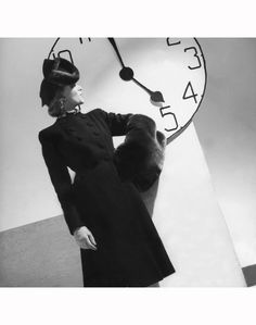 Model, standing, in profile with her hand on her hip, by a clock, wearing a collarless black wool coat, with muff and hat of beaver-dyed Laskin lamb Vogue 1939
