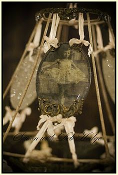what a beautiful way to display vintage photos...tied to a vintage wire lampshade...love <3