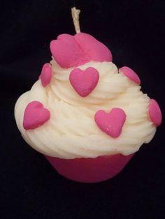 Vela em formato de cupcake, na cor branca com corações na cor rosa escuro, produzida em cera a base de óleo vegetal de fonte renovável, acondicionada em caixa de acetato transparente e palha. Pode ser aromatizada nas essências de morango, baunilha e chocolate. <br> <br>Vela pintada a mão com tinta a base de água.