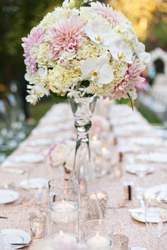 A beautiful mix of flowers, including orchids and dahlias, make up this tall floral centerpiece.