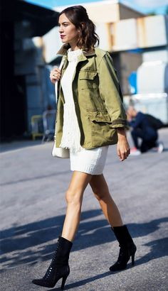Alexa Chung wears a white knit dress with fringe, an army jacket, and black boots
