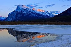 Mount Rundle appears cold and crisp during winter at dusk as it overshadows the partially frozen Vermillion Lake near the town of Banff in Alberta, Canada. This is in Banff National Park, which forms part of the Canadian Rocky Mountain Parks. Banff National Park Hotels, Banff National Park Canada, National Park Camping, National Parks, Lake Pictures, Parks Canada, Mountain Park, Camping Photography