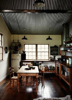 This kitchen has a corrugated metal ceiling and side wall. The dark and rough surface draws the eyes upwards in this room. It gives the room a rustic and country feel to it. I think it makes the room feel a bit smaller, than a light colour paint would do. Corrugated Tin Ceiling, Metal Ceiling, Metal Roof, Black Ceiling, Ceiling Lighting, Porch Ceiling, Ceiling Panels, Corrugated Sheets, Drop Ceiling Tiles