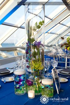 A Peacock cylinder vase centerpiece  with multiple water-filled glass vases varying in size. White circular candles are placed on two smaller vases. An overall great centerpiece decor idea for the modern wedding.