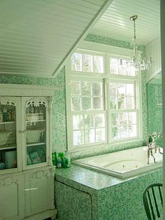 Aqua glass tiles meet up with the angled beadboard ceiling.