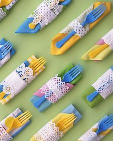 Fold two different napkins together. Cut a strip from a round or square paper doily; for a band that's lacy on both edges, accordion-fold a small doily in the middle. Wrap it around napkin; tape at back. Tuck in a plastic fork.