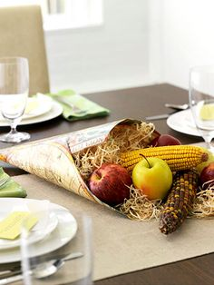 Classic Cornucopia  Add color and texture to your harvest table with a cornucopia spilling over with apples, dried corn, and shredded paper. Craft your own by folding a sheet of gift wrap or decorative paper into a cone shape and securing the edges with tape.