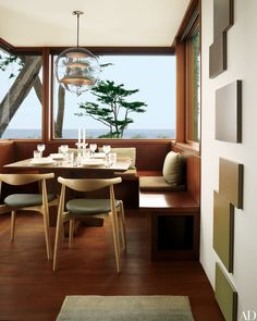 A view of the ocean from the breakfast room of a California home. Verner Panton's acrylic Globe light hangs above Hans Wegner CH20 Elbow Chairs, and Marie Krane Bergman paintings are displayed on the wall.