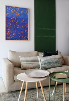 The artwork is by Lana's brother, Byron Fredericks, and the green metal sheet was originally used on one of Lana's shoots as a backdrop. The cushions on the sofa are from Evolution Product and the ceramic platter is from Dayfeels.