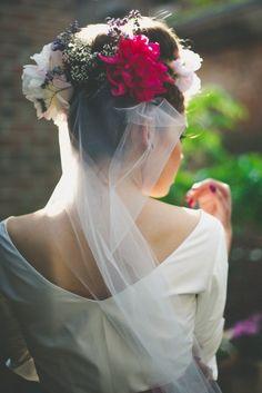 Brautfrisur mit Blumenkranz und Schleier zum schlichten Hochzeitskleid mit V-Ausschnitt im Rücken, Trägern und Ärmeln (www.noni-mode.de - Foto: Le Hai Linh)