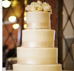 Trish and Steve's four-tiered round cake took on an a clean–lined look, frosted with white buttercream and adorned with ivory ribbon and a strand of rhinestones. Simple white roses graced the top.