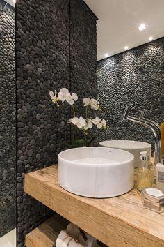 Em conexão com a rusticidade do mosaico, para o lavabo foram especificados seixos pretos telados (Asia Pedras) e bancada de madeira.