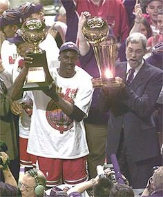 Jordan and Phil Jackson display the hardware that comes with winning the 1998 NBA Championship. Michael displays the Finals MVP trophy, Phil the Larry O'Brien trophy.
