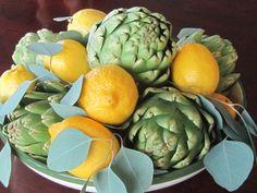 Zitronen und Artischocken in einem Teller auf dem Tisch als Deko