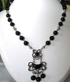 Its a unique one-of-a-kind piece!  Collar de bolas de Ónix negro con un colgante de diseño gallego en Plata de ley 925, con incrustaciones de auténtico Azabache asturiano en dos cabujones. Está engarzado a mano con alambre de Plata de ley de 0,7 mm. y lleva intercaladas bolas de plata.  El collar mide 47 cm. El colgante es de 6 cm. Las bolas de onix son de 8 mm. y las bolas de plata son de 6, 5 y 4 mm. Lleva un cierre de reasa de plata.  Hay muy pocas minas de Azabache en todo el mundo. Este…