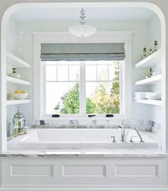 Bathtub Organization    Shelves near the tub are an easily accessible place to keep a store of bath salts and soaps in vintage containers. The handy location also ensures that books and fluffy white towels are always within reach.