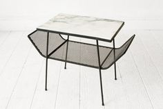 A beautiful mid century coffee table. Minimal iron frame with a piece of marble for the table top. Two tiers, the second mesh tier has magazine