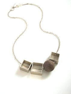 B.DIFFERENT necklace. three palladium-plated squares and a lava stone on a palladium-plated chain.