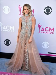 Hot metal! Carrie Underwood oozed glamour at the ACM Awards red carpet in Las Vegas on Sunday in a gorgeous sparkling gown with tulle nude train